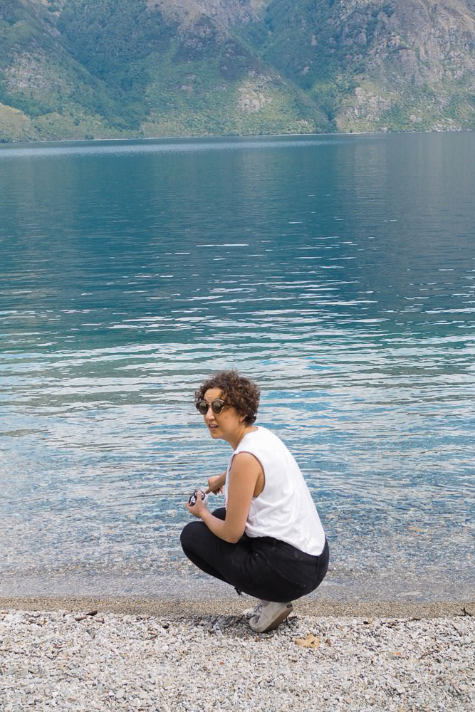 Woman crouched down by lake's edge