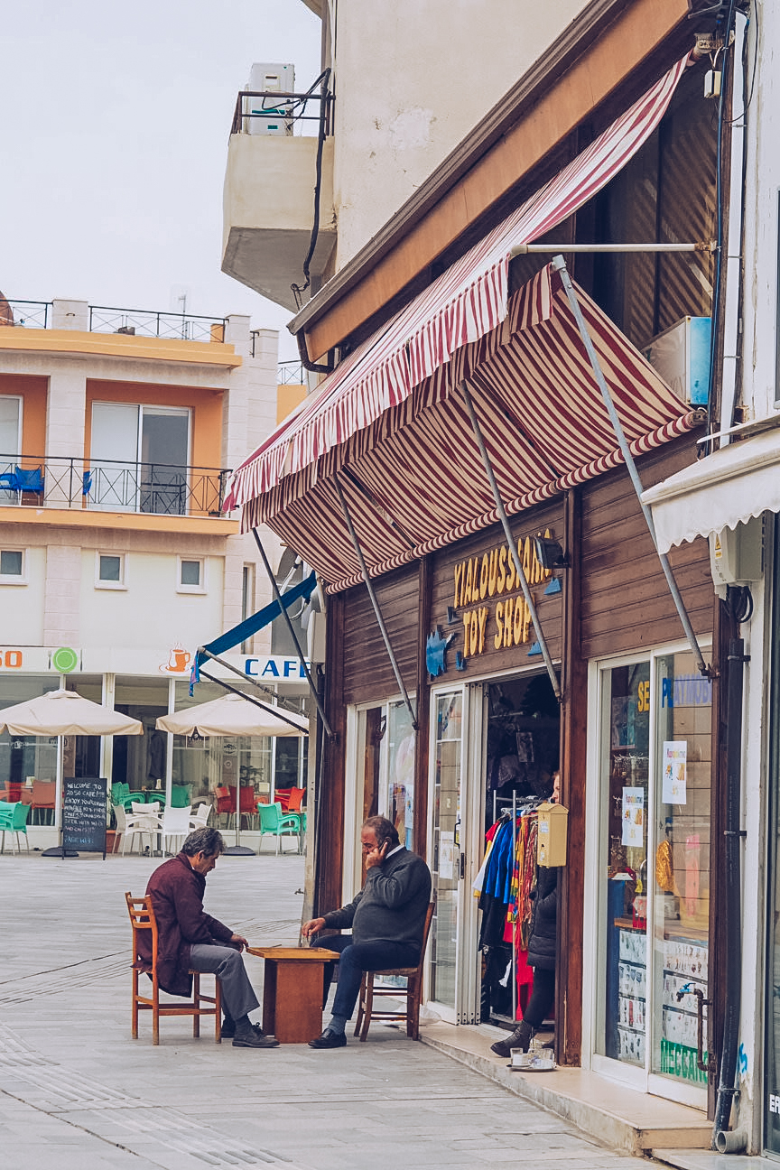 old men playing backgammon outside a shop