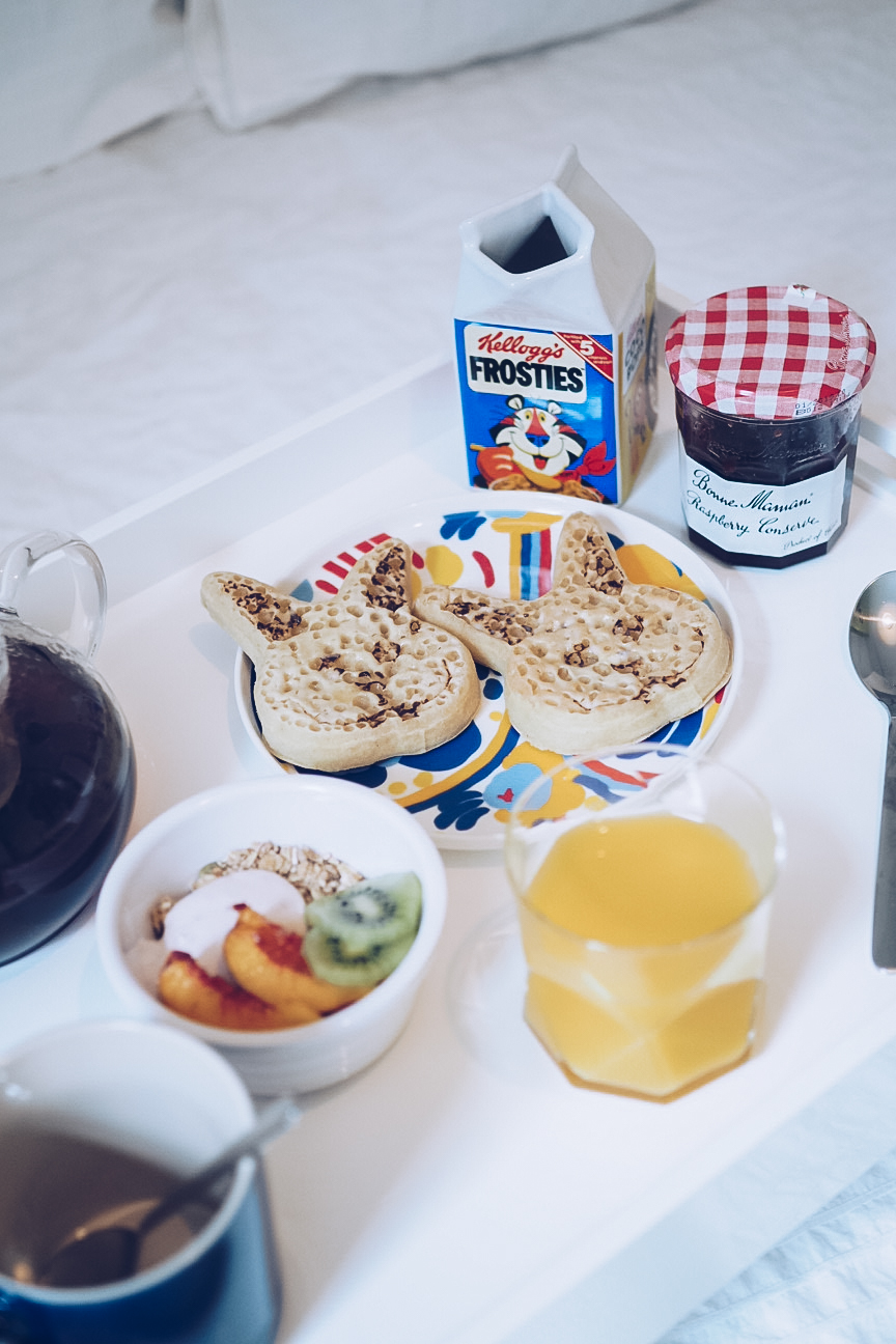 breakfast in bed tray with crumpets, jam, granola and orange juice