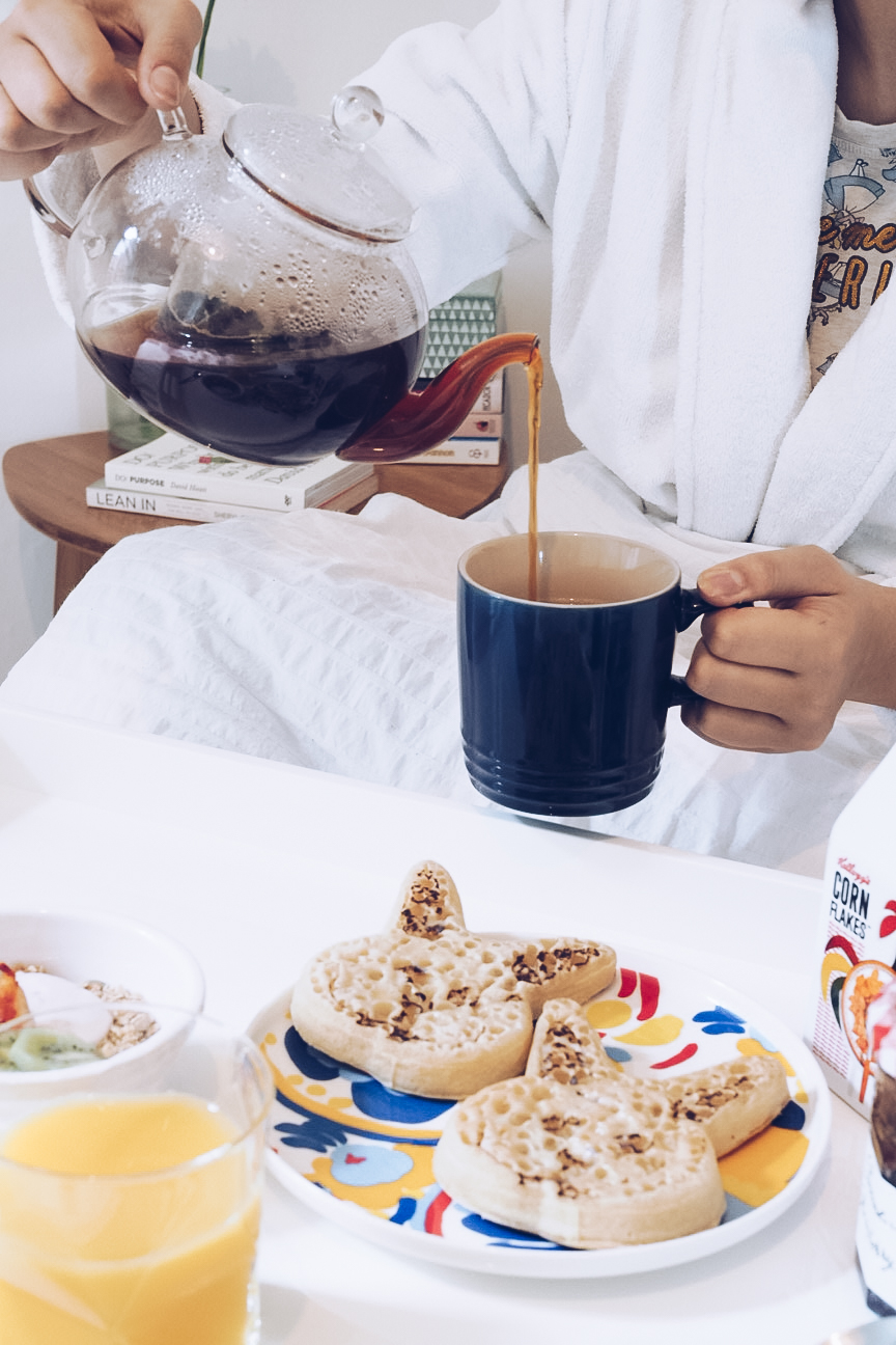 pouring tea from a glass teapot, rabbit shaped crumpets on plate