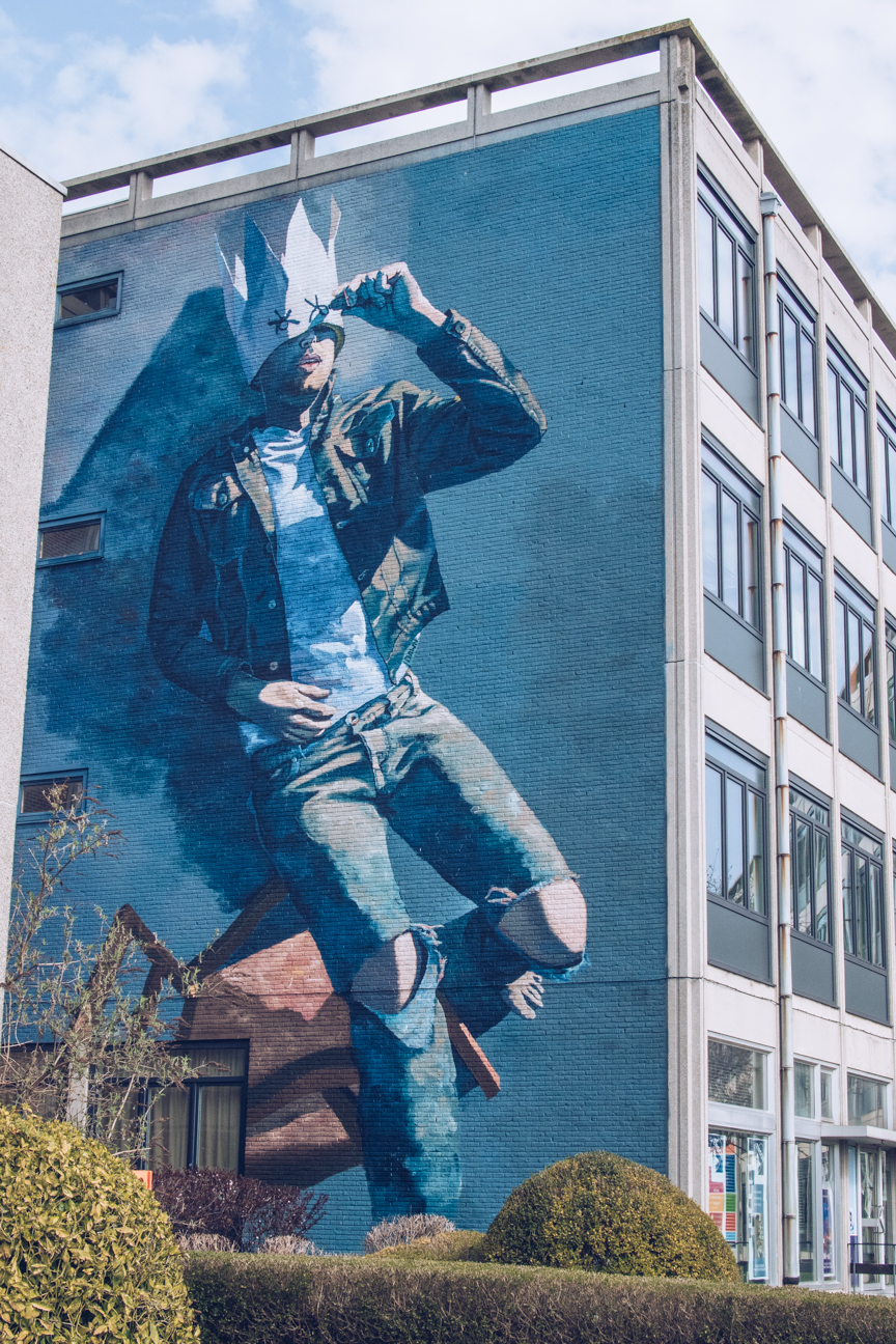 Street art mural of boy in ripped jeans