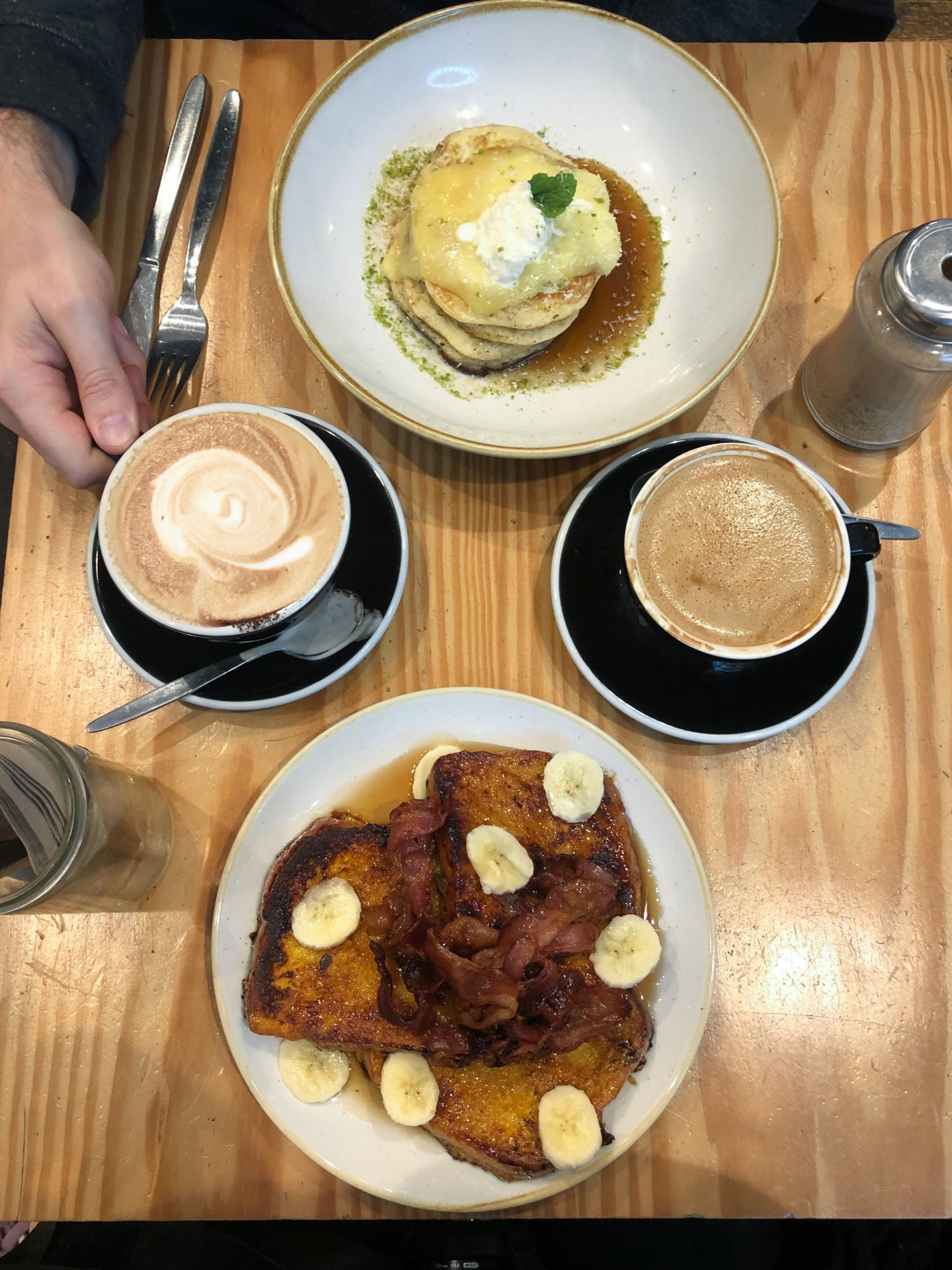 flatlay of brunch with two coffees, french toast and pistachio pancakes