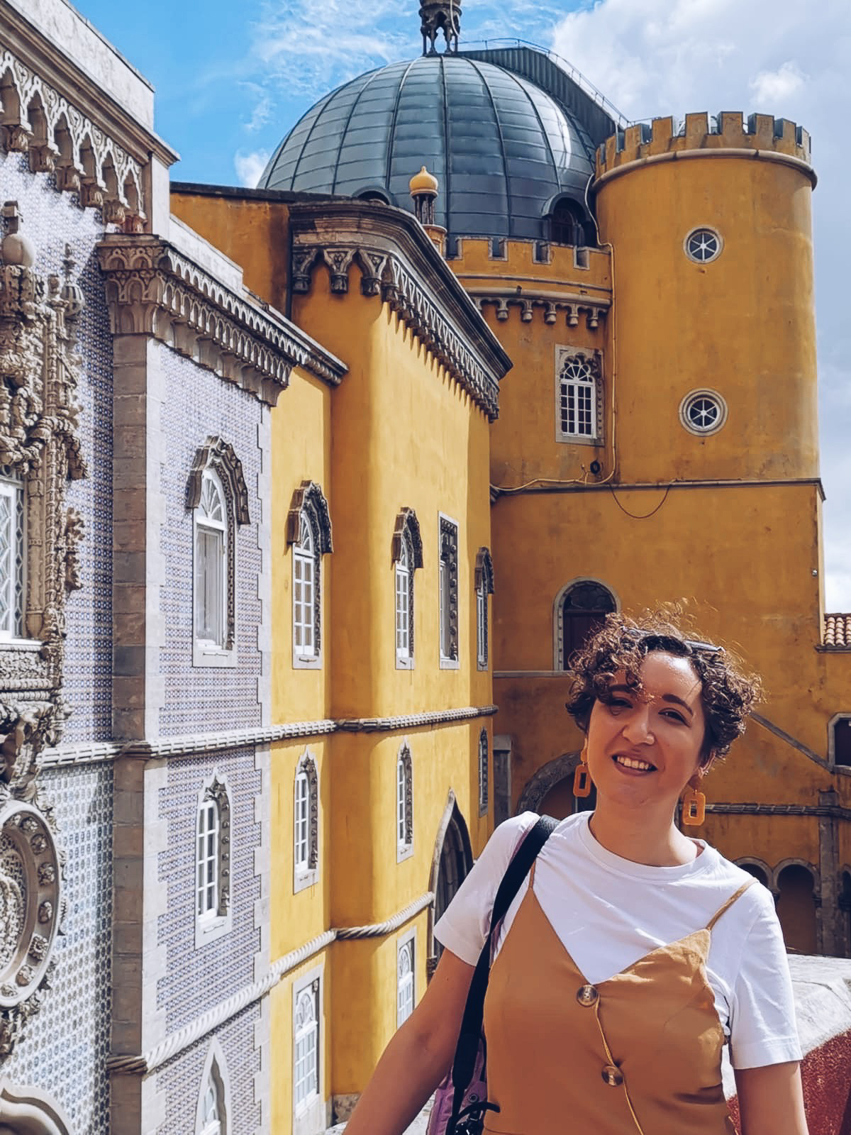 woman in yellow dress in front of yellow palace in sintra