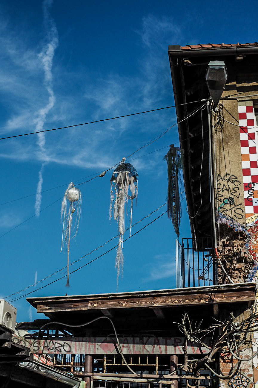jellyfish art hanging from houses in metelkova