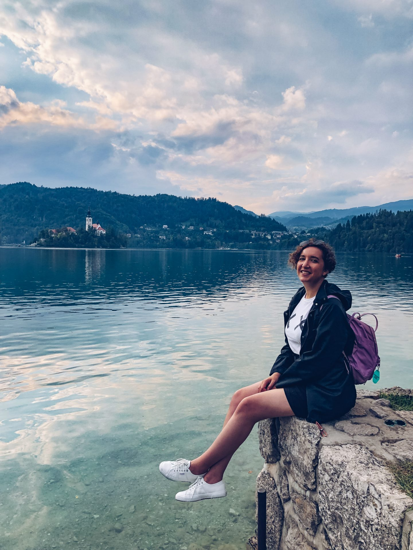woman sat by the water of Lake Bled, Slovenia