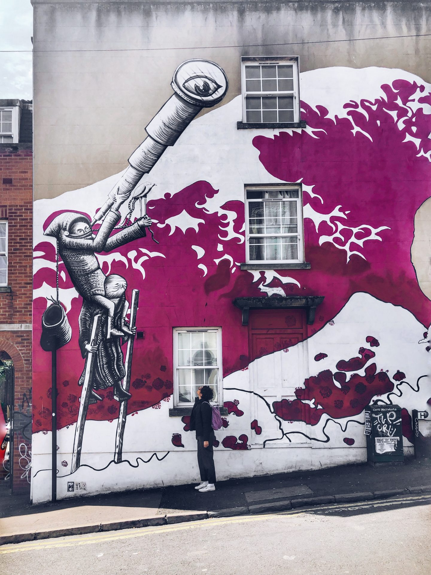 woman in front of street art showing a tsunami of roses and a man with a telescope