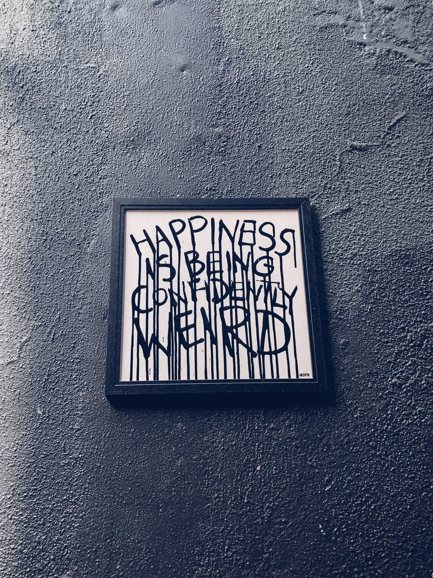 a white canvas in black frame on a black wall. the canvas has the words 'happiness is being confidently weird' painted on it