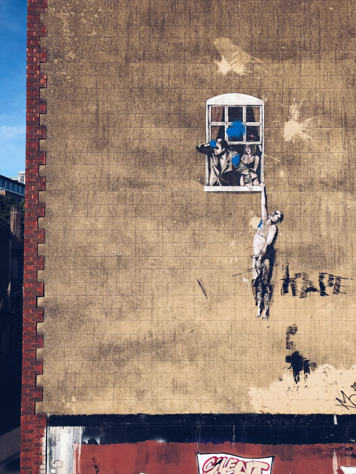 banksy's hanged man is on the side of tall brick building and shows a window with a man looking out of it, his wife is behind him looking nervous and a naked man is hanging on my his hand to the windowsill