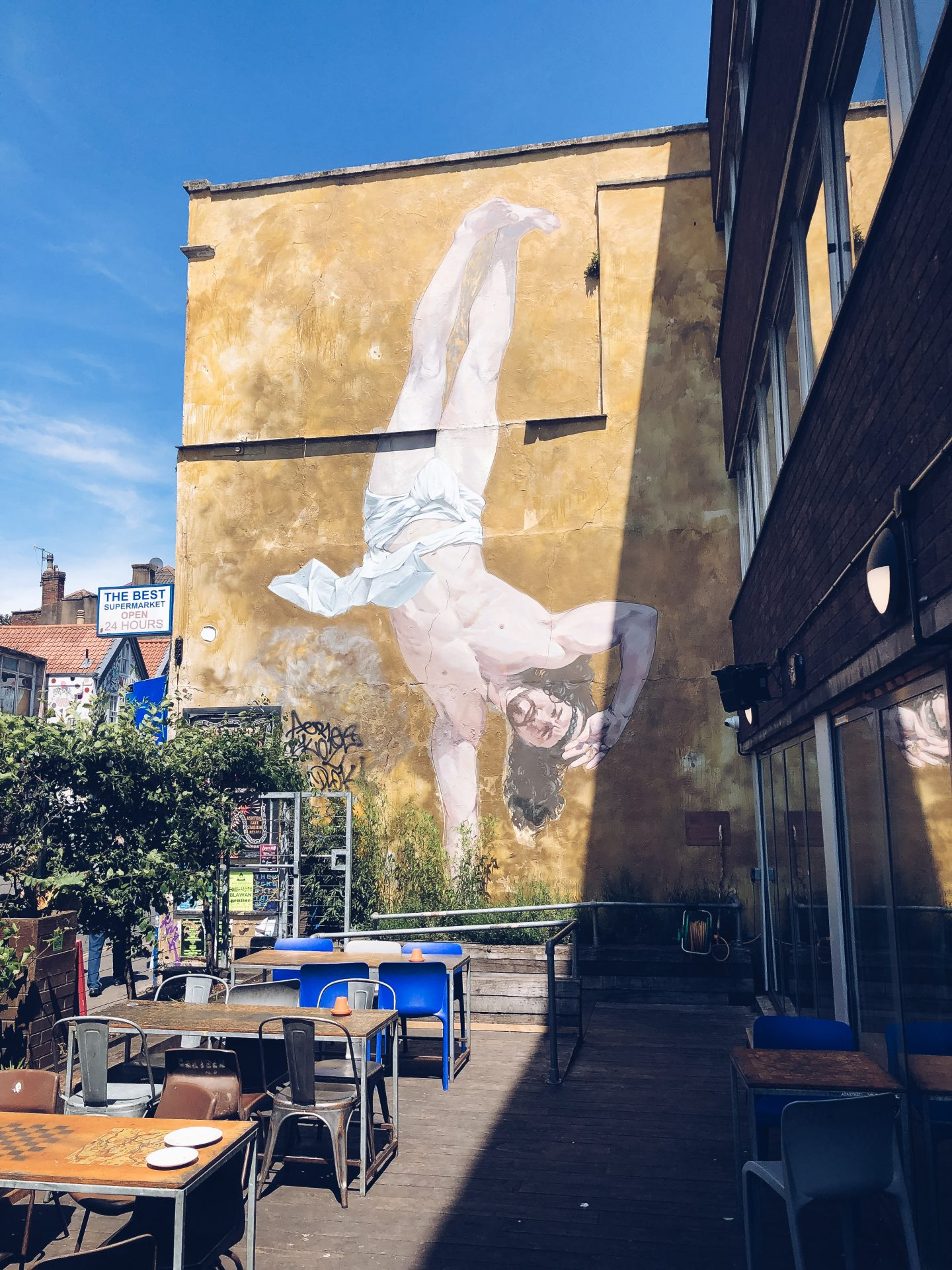 cosmo sarson's breakdancing jesus mural is on a wall in an enclosed outdoor cafe space