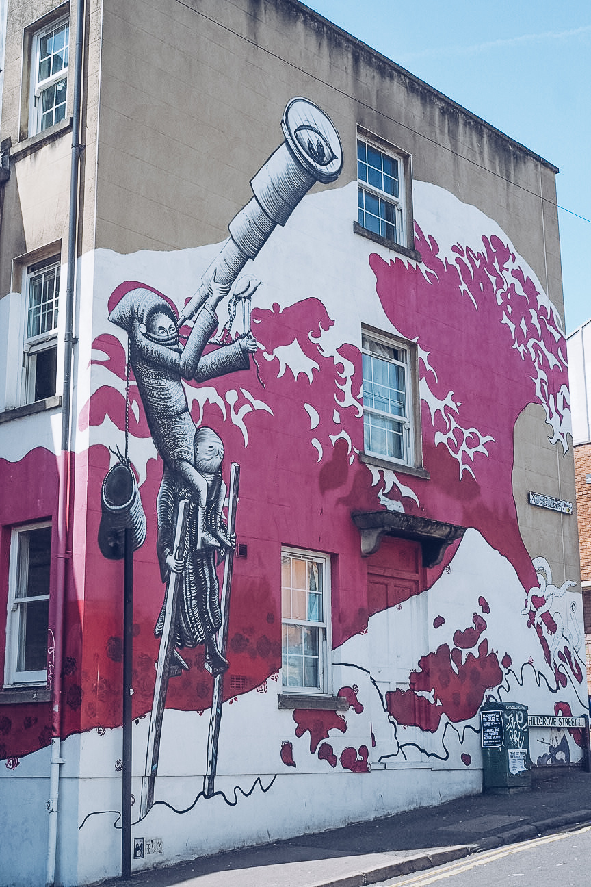 phlegm's tsunami of roses is a large wave of crimson and white roses with a man holding a telescope on it. the mural is on the side of a two storey house.