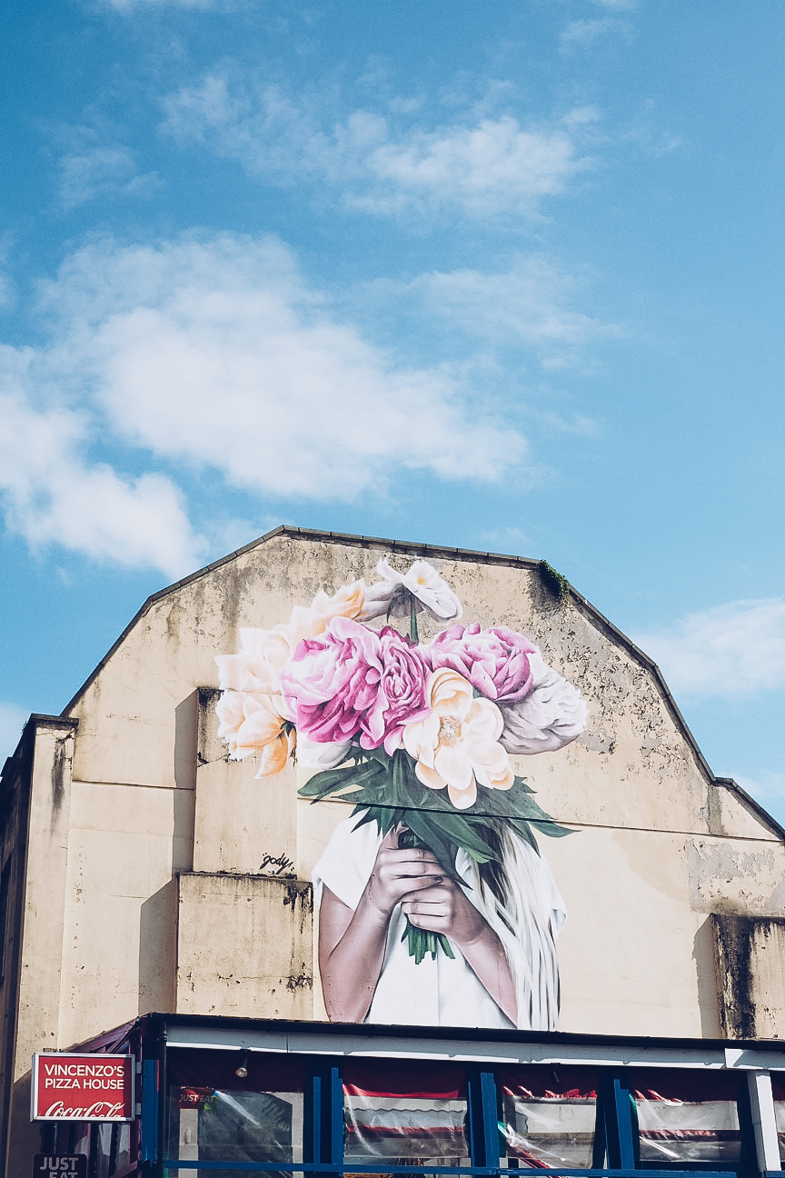the florist by jody thomas shows a person holding a large bunch of flowers in front of their face. the mural is very large and on the side of a building above a shop and there is blue sky with a few clouds.