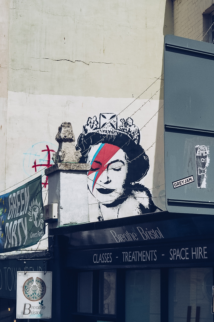 a black and white portait of the queen at a young age with a blue and red lightning bolt across her face can be seen above a shop front