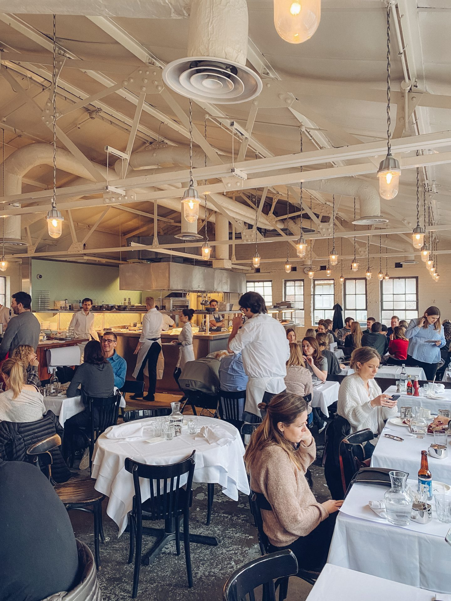 tables full of people in a warehouse space with tall ceilings, white walls and an open kitchen in the background