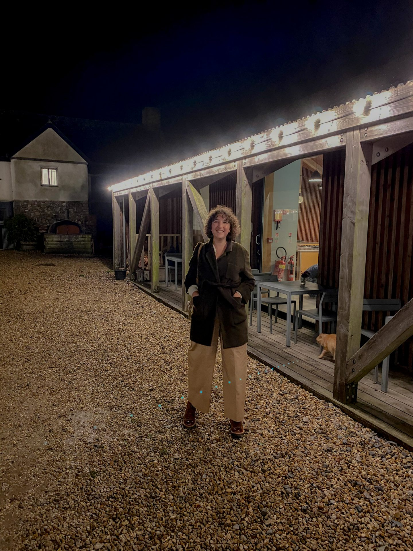 charlie is stood outside the veranda of river cottage at night with fairy lights hanging from the roof