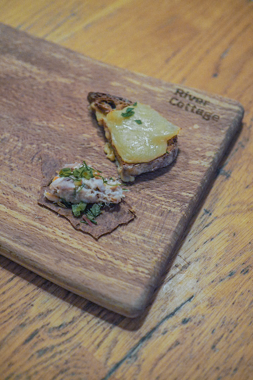 roasted onion rarebit canape and smoked mackerel pate on a fennel rye cracker, both serves on a wooden chopping board
