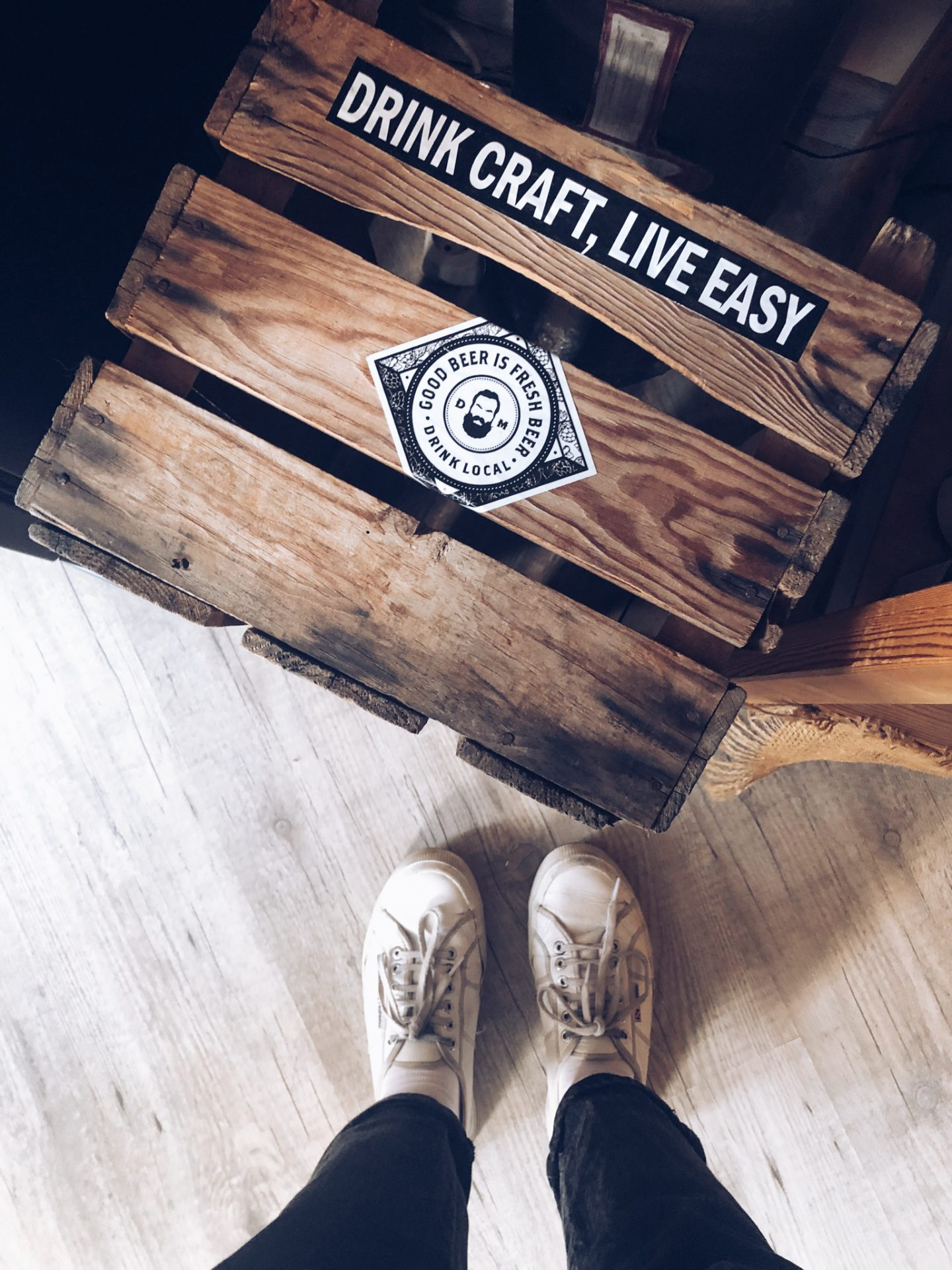 looking down on charlie's feet in white trainers, stood next to a wooden crate with a sticker that says 'drink craft, live easy'