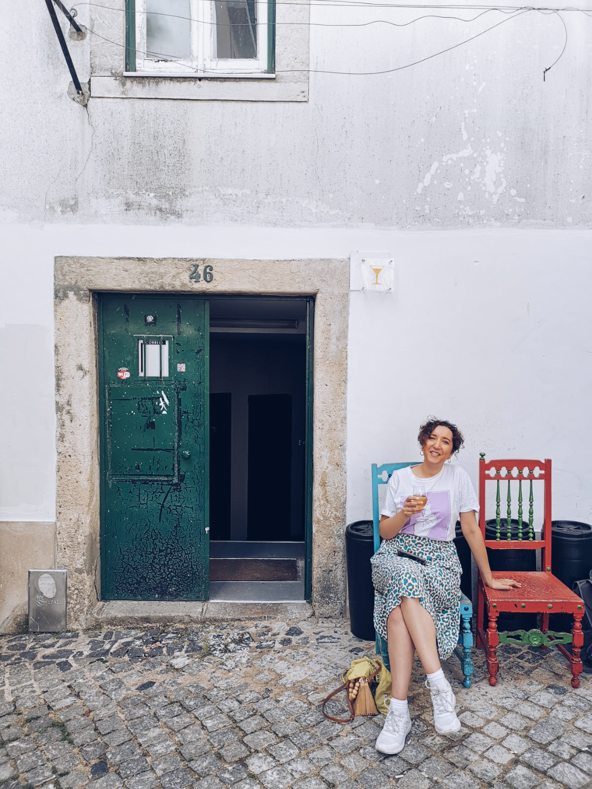 charlie is wearing a white and green leopard print skirt with a white and purple tshirt. She is holding a pint of beer and is sat on a red wooden chair on some cobbles at the back door of a pub in Lisbon.