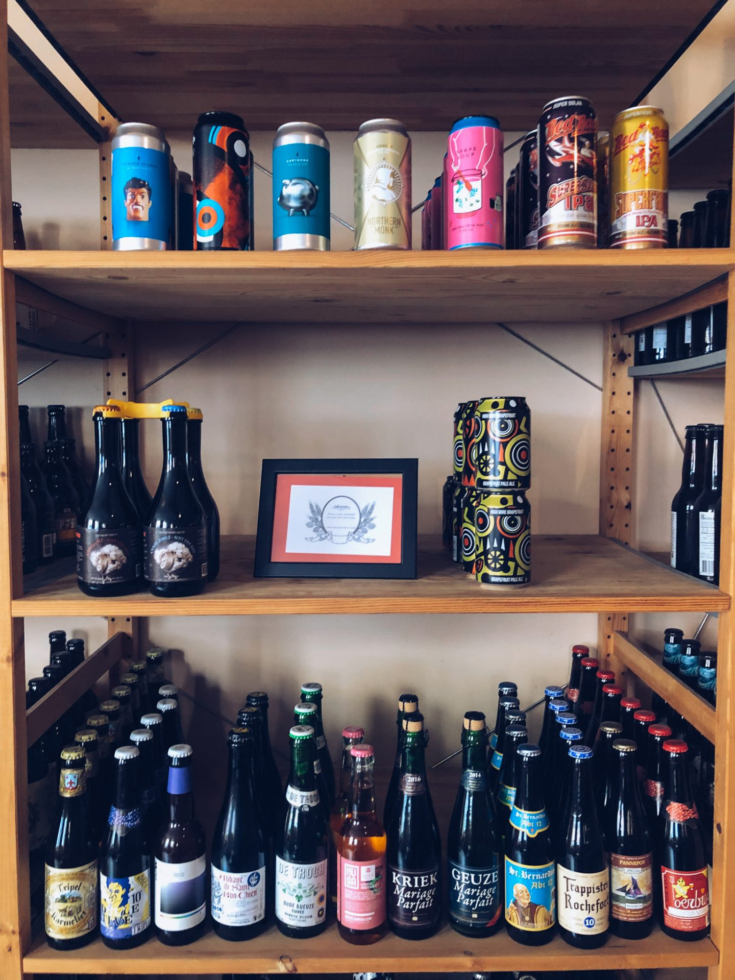 three shelves full of various bottle and cans of craft beer